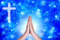 Praying hands over a blue sky with crucifix royalty free stock photo