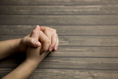 Praying Hands. On a Wooden Background royalty free stock image