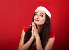 Praying happy woman in santa claus christmas costume looking up Royalty Free Stock Image
