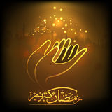 Praying human hands with Arabic calligraphy for Ramadan Kareem celebration. Royalty Free Stock Image