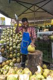 Coconut fruit juice seller. BATU CAVE, 22 August 2018 - Man cutting the coconut fruit freeing the juice inside to be sold to passer by tourists thirsty after royalty free stock photography