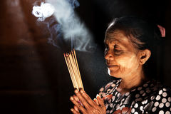 Praying with incense sticks. Old wrinkled traditional Asian woman praying with incense sticks inside a temple, low light with smoke and beautiful natural royalty free stock photo