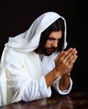 Praying Jesus Christ of Nazareth. Kneeling hands together Stock Image