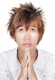Praying Korean teen portrait. Closeup portrait of angelic emo Korean teenager with orange dyed hair, looking up sadly and solemnly and begging with hands praying Royalty Free Stock Photo