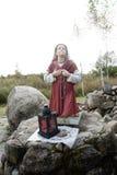 Praying with a lantern. Faience figure kneeling nun with red lantern Royalty Free Stock Photo