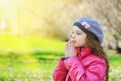Praying little girl in spring park. Praying cute  girl in spring park Stock Photography