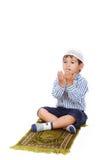 Praying little kid. A little muslim kid is praying on traditional way Royalty Free Stock Image