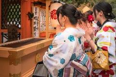 Praying for love at Kiyomizu-dera in Kyoto, Japan. Kyoto, Japan -November 2, 2018: Young girls in traditional Japanese costume praying in front of Jinja-Jishu royalty free stock photography