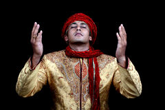 Praying Man. A rich young Afghan man in prayers, on black studio background stock photo