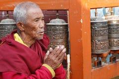 Praying man. Old monk reads mantra near praying mills, Bodnath stupa (Boudha), Kathmandu, Nepal, 2009 Stock Images