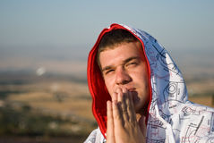 Praying Man. With folded hands and hood on his head Royalty Free Stock Images