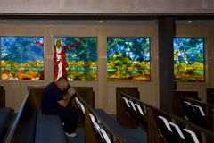 Praying Man. Man praying in fornt of a stained glass window royalty free stock photography