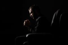 Praying Man. Man with Beard Sitting on a Armchair Praying Royalty Free Stock Images