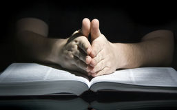 Praying man and bible. A man sitting at a table, his hands in a praying gesture royalty free stock image