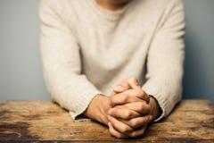 Praying man at desk Stock Photo