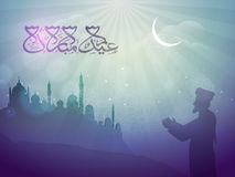 Praying Man in front of Mosque for Eid. Silhouette of Religious Muslim Man offering Namaz in front of a Mosque in night, Islamic Background with Arabic Royalty Free Stock Photography