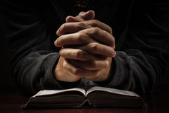 Praying. Man hand and bible on desk Stock Images