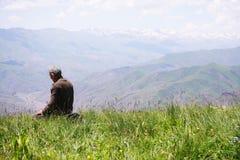Praying man kneeling rear view Stock Photography