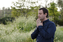 Praying man outdoors in a grassy field. Royalty Free Stock Photography