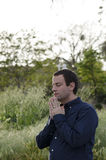 Praying man outdoors in a grassy field. Royalty Free Stock Photo