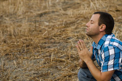 Praying man. Man praying outside on a hill with his hands together Stock Images