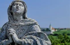 Praying Mary no.1. Statue of a praying female saint at a Calvary Stock Photos