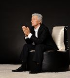 Praying mature businessman sitting in chair Royalty Free Stock Photography