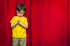 Praying Mixed Race Boy in Front of Red Curtain Stock Image