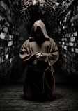 Praying monk in dark temple corridor Royalty Free Stock Photography