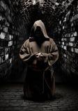 Praying monk in dark temple corridor. Mystery monk praying on kneels in dark temple corridor Royalty Free Stock Photography