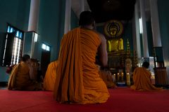 Monks praying in a buddhist temple stock photo