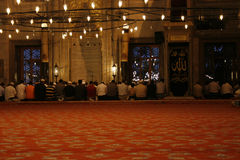 Praying at Mosque. Men sitting on knees and praying during Ramadan in Blue Mosque, Istanbul in Turkey Royalty Free Stock Photo