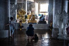 Praying mother and playing child in a Buddhist temple in Thailand. stock image
