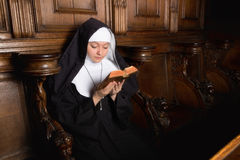 Praying novice nun. Novice nun reading a prayer book (shot in a 17th century church interior, all clothing and accessories authentic or antique stock image