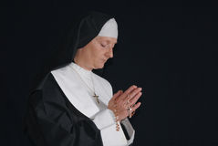 Praying nun. Middle aged devout nun in deep thoughts, praying.  Religion, christianity, lifestyle concept Stock Photography