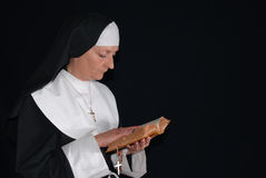 Praying nun. Middle aged devout nun in deep thoughts, praying.  Religion, christianity, lifestyle concept Royalty Free Stock Photography