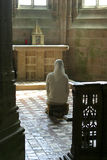 Praying nun in church. Kneeled praying nun in the abbey of Mont Saint-Michel (Normandy) in France Royalty Free Stock Photography