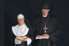 Praying nun and priest. Middle aged devout nun and priest in deep thoughts, praying.  Religion, christianity, lifestyle concept Royalty Free Stock Image