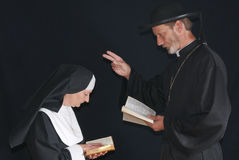 Praying nun and priest. Middle aged devout nun and priest in deep thoughts, praying.  Priest blessing nun Royalty Free Stock Images