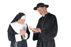 Praying nun and priest. Middle aged devout nun and priest in deep thoughts, praying. Female hands crossed, male with bible in hand Royalty Free Stock Images