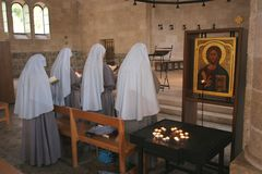 Praying nuns. View of praying nuns inside The Church of the Multiplication of the Loaves and the Fishes, Tabgha, Israel Stock Photo