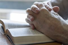 Praying Old Hands. Weathered old man's hands clasped in prayer over open Bible Royalty Free Stock Photography