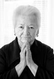 Praying old woman Stock Image