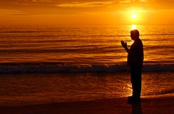 Praying with Orange Sunset Royalty Free Stock Images