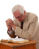 Praying Pastor. Senior pastor kneeling in prayer over an opened Bible that's on a small child's school desk royalty free stock photo