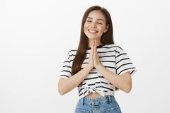 Praying for peace and health for family members. Relaxed carefree attractive european female, closing eyes and smiling. Joyfully, holding hands in pray while stock images