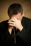 Praying priest Stock Images