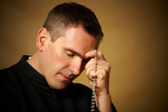 Praying priest. With rosary in his hands Stock Photos