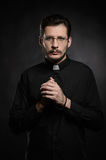 Praying priest. Portrait of priest standing isolated on black Stock Photography
