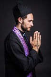 Praying priest. Studio portrait on black background Stock Image